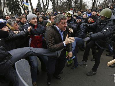 Manifestantes contrarios al gobierno de Yanukovich agreden en Kiev a Vitaly Gruchevsky, diputado del Partido de las Regiones, frente a la sede de la Duma, el 22 de febrero de 2014.