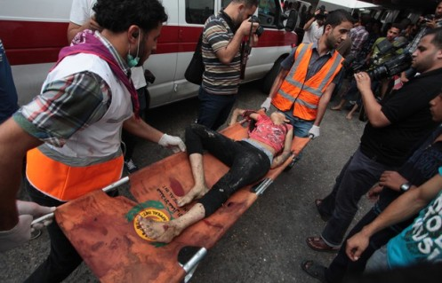 A Palestinian medics carries the body of girl, whop was killed during Israeli shelling,