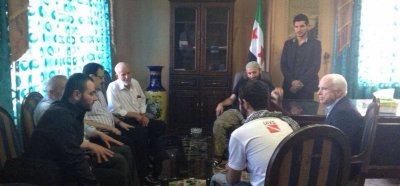 """John McCain se reúne en Siria con el Estado Mayor del Ejército Sirio Libre (ESL). A la izquierda, en primer plano, Ibrahim al-Badri (el hoy autoproclamado """"califa"""" Ibrahim) escucha al senador, quien habla diractamente al futuro """"califa"""". El individuo con espejuelos es el general Salim Idriss, jefe del ESL."""