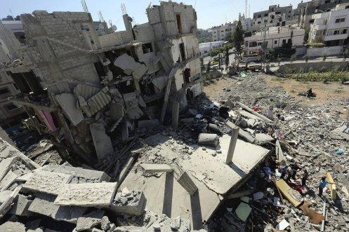 """GAZ20 CIUDAD DE GAZA (FRANJA DE GAZA) 11/07/2014.- Miembros de la familia Abu Lealla inspeccionan los escombros de su casa tras un bombardeo israelí registrado en el norte de la ciudad de Gaza, hoy, viernes 11 de julio de 2014. Noventa y ocho palestinos han muerto y más de 600 han resultado heridos en la Franja de Gaza desde el inicio de la operación militar israelí """"Margen Protector"""", que hoy entra en su cuarto día, informaron medios locales. EFE/Mohammed Saber"""