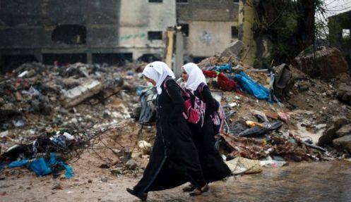 Niñas estudiantes palestinas Gaza caminan por los escombros de una casa destruida durante el ataque de 2014 en Beit Hanoun, al norte de la Franja de Gaza, el 12 de abril de 2015. / Reuters