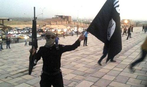 Un luchador Estado Islámico blande la bandera de color negro azabache del grupo radical