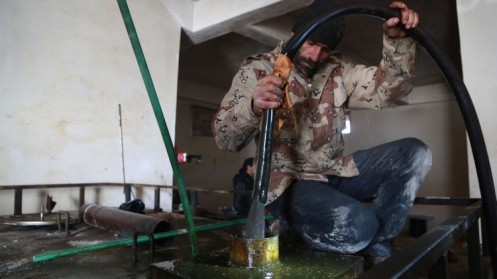 A man pours crude oil into a tank inside a make-shift refinery in the Aleppo countryside January 13, 2015. Residents of Kafr Hamra, a town in the rural Aleppo countryside, refine crude oil in makeshift cottage refineries in warehouses and backyards for heating, operating bakeries and even running cars, just like most locals across rebel-held areas of Syria. The state no longer pumps gasoline to areas in rebel hands, and civilians have resorted to buying crude oil from armed groups who have taken over major oil producing areas in the east since 2012. Islamic State is currently in control of oil wells, and civilian middlemen now buy crude from the group before reselling it to locals, but the practice predates Islamic State's capture of oil wells from rival groups. REUTERS/Nour Kelze(SYRIA - Tags: BUSINESS COMMODITIES ENERGY POLITICS CIVIL UNREST CONFLICT) ATTENTION EDITORS: PICTURE 05 OF 18 FOR WIDER IMAGE PACKAGE 'FUELLING THE ISLAMIC STATE ECONOMY' TO FIND ALL IMAGES SEARCH 'NOUR GASOLINE' - RTR4LYSJ